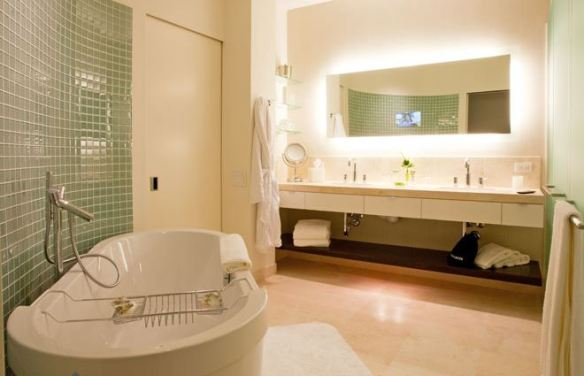 The bathroom has all the amenities, including a TV in the mirror.